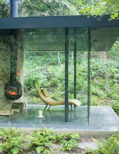log fire and retro chair in glass pavilion