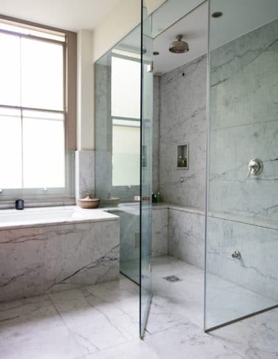 walk in shower with marble surround